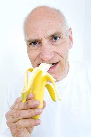peeled banana: Senior man biting on peeled banana Stock Photo