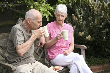 Senior man and woman enjoying their teatime in the park photo