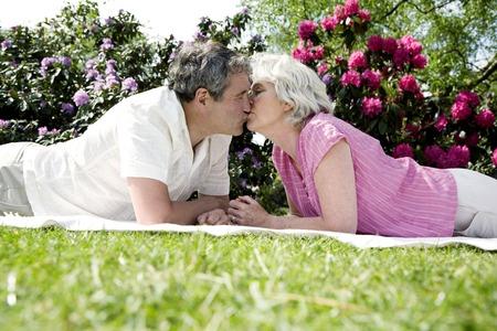 picnic blanket: Senior hombre y una mujer bes�ndose mientras se est� acostado hacia adelante en la manta de picnic