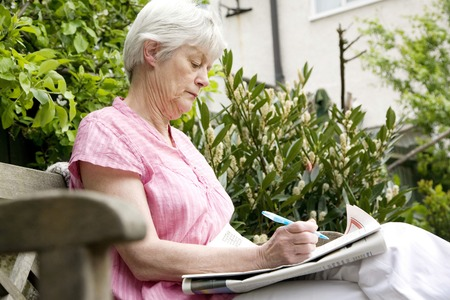 Senior woman writing on newspaper photo