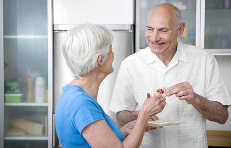 Senior man and woman drinking coffee together photo