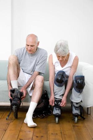 Senior man and woman preparing for inline skating photo