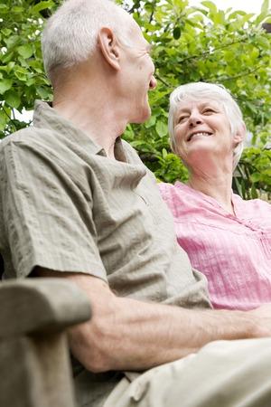 Senior man and woman sitting on bench photo
