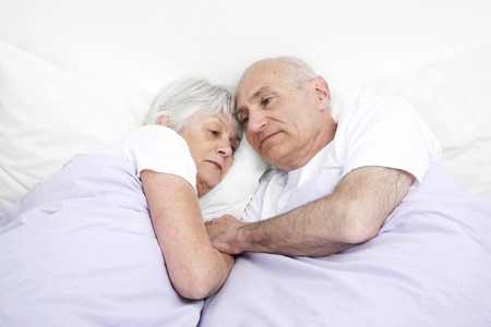 Senior man and woman contemplating while sleeping together