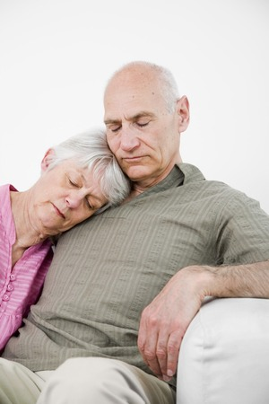 Senior man and woman taking a nap on the couch photo