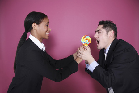 Businessman grabbing lollipop from businesswoman photo