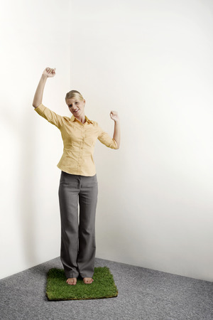 jubilating: Businesswoman standing on a patch of grass shaking fist in victory