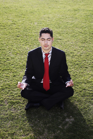 Businessman meditating on the field photo
