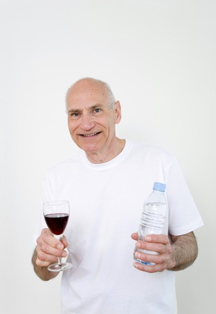 Senior man holding a glass of wine on one hand and bottled water on the other