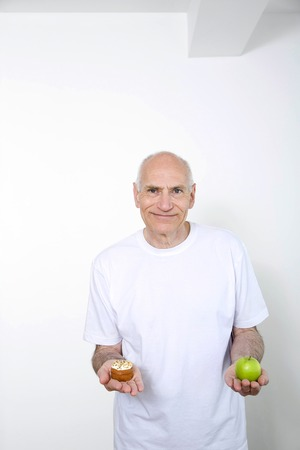 Senior man holding cake in one hand and green apple in the other photo