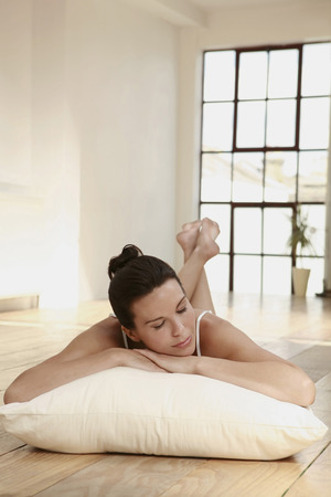 lays forward: Woman lying on pillow with legs up
