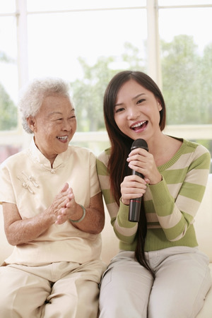 Woman singing into the microphone, senior woman clapping hands photo