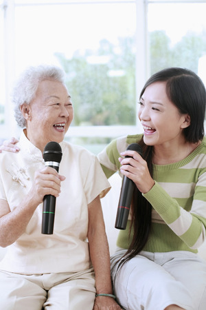 Woman and senior woman singing into the microphones photo