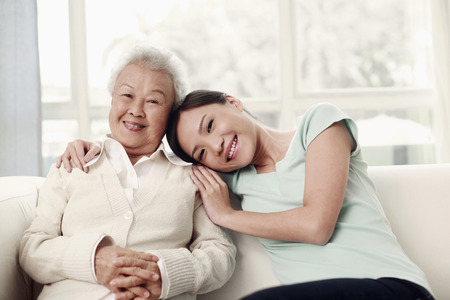 Woman resting her head on senior womans shoulder photo