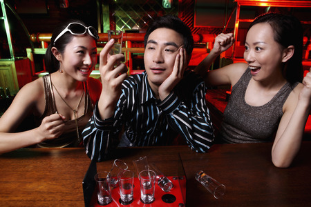 shooters: Man drinking shooters, women cheering him