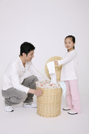 Girl throwing clothes into laundry basket, man watching photo