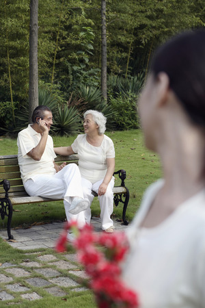 Senior man talking on the phone with senior woman sitting beside him, woman holding a bouquet of flowers looking at them photo