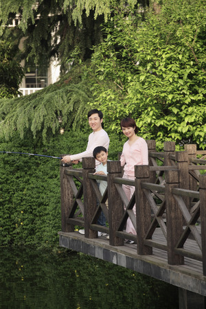 Man fishing, woman and boy smiling photo