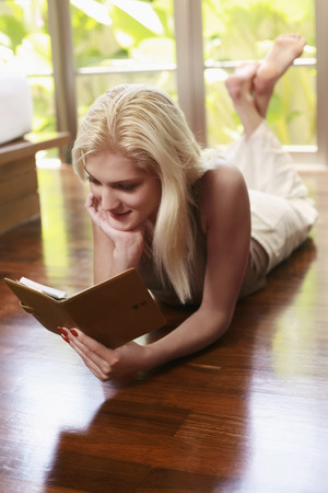 lays forward: Woman lying forward reading an organizer with her legs up Stock Photo