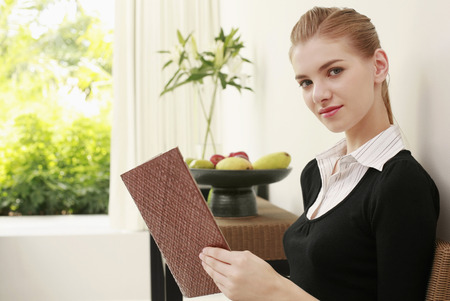 Woman in formal wear holding a book, looking at the camera
