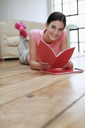 Woman lying forward on the floor reading book