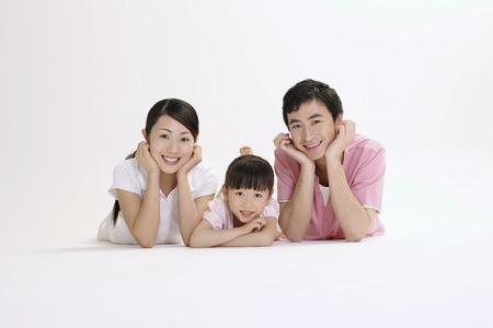 Mężczyzna, kobieta i dziewczynka leży do przodu uśmiecha