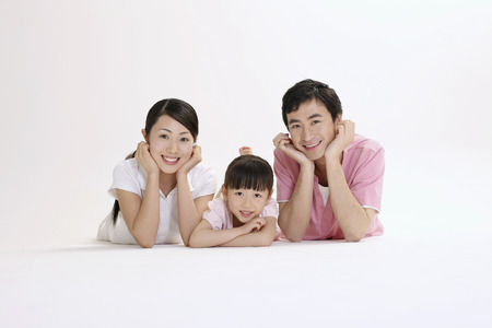Man, woman and girl lying forward smiling