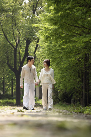 Man and woman holding hands while walking in the park photo