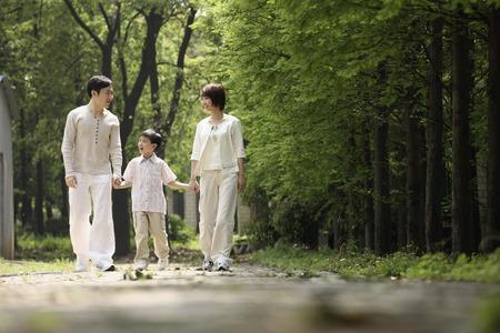 공원에서 산책하는 동안 부모와 손을 잡고 소년