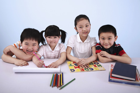 four person only: Children studying together