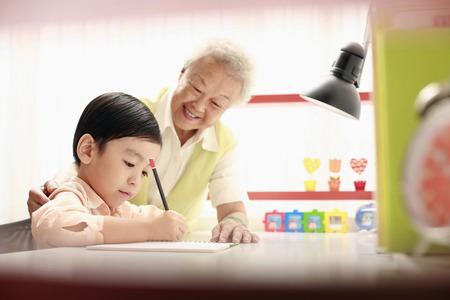 Starszy kobieta pomaga chłopcu z jego pracy domowej