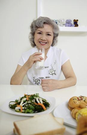 Senior woman drinking milk photo