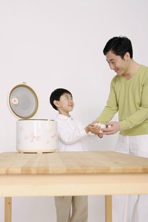 rice cooker: Boy passing a bowl of rice to man Stock Photo