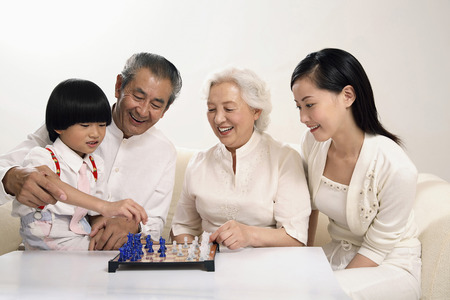 Boy playing chess game with senior woman, woman and senior man watching photo