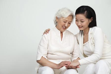 Senior woman holding womans hand