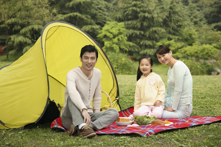 Girl and parents having picnic in the park photo