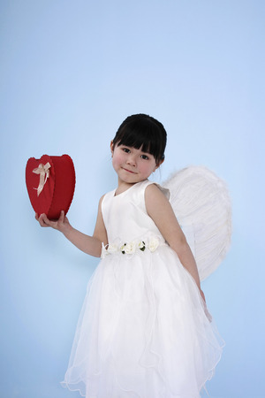 Girl wearing white dress with angel wings holding red heart-shaped box photo