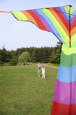 Girl and woman flying kite in the park photo