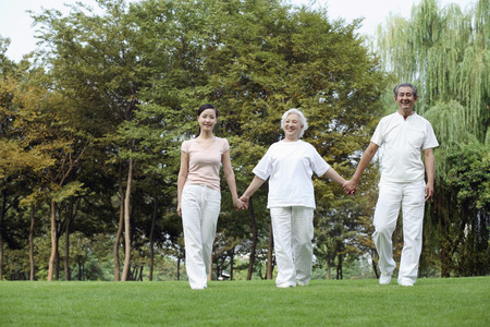 Woman together with senior couple holding hands while walking in the park Stock Photo - 26241778