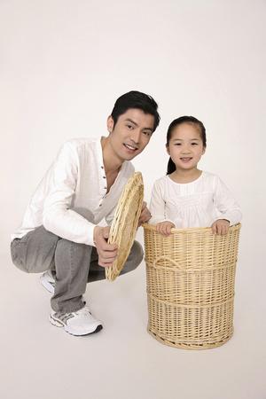 Girl hiding inside laundry basket, man squatting beside her photo