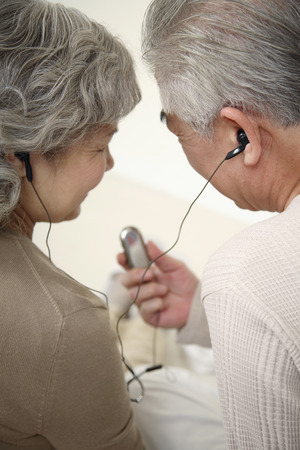 Senior couple listening to music on portable MP3 player Stock Photo