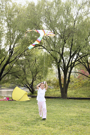 Girl running while flying a kite photo
