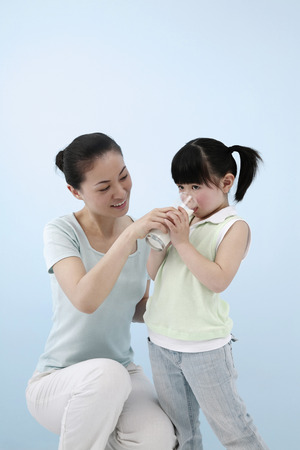 Woman holding a glass of milk for girl to drink