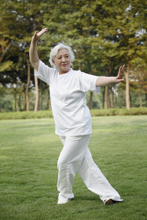 Senior woman practising tai chi in the park