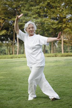 Starszy kobieta ćwiczenia tai chi w parku