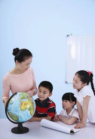 Woman teaching boy and girls how to read the globe photo