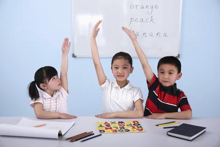 Children raising hands in classroom