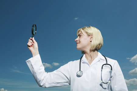 Woman holding up magnifying glass photo