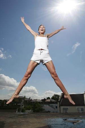 legs apart: La mujer que salta hacia arriba, las manos y las piernas separadas