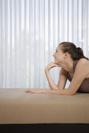 Woman lying forward on sofa
